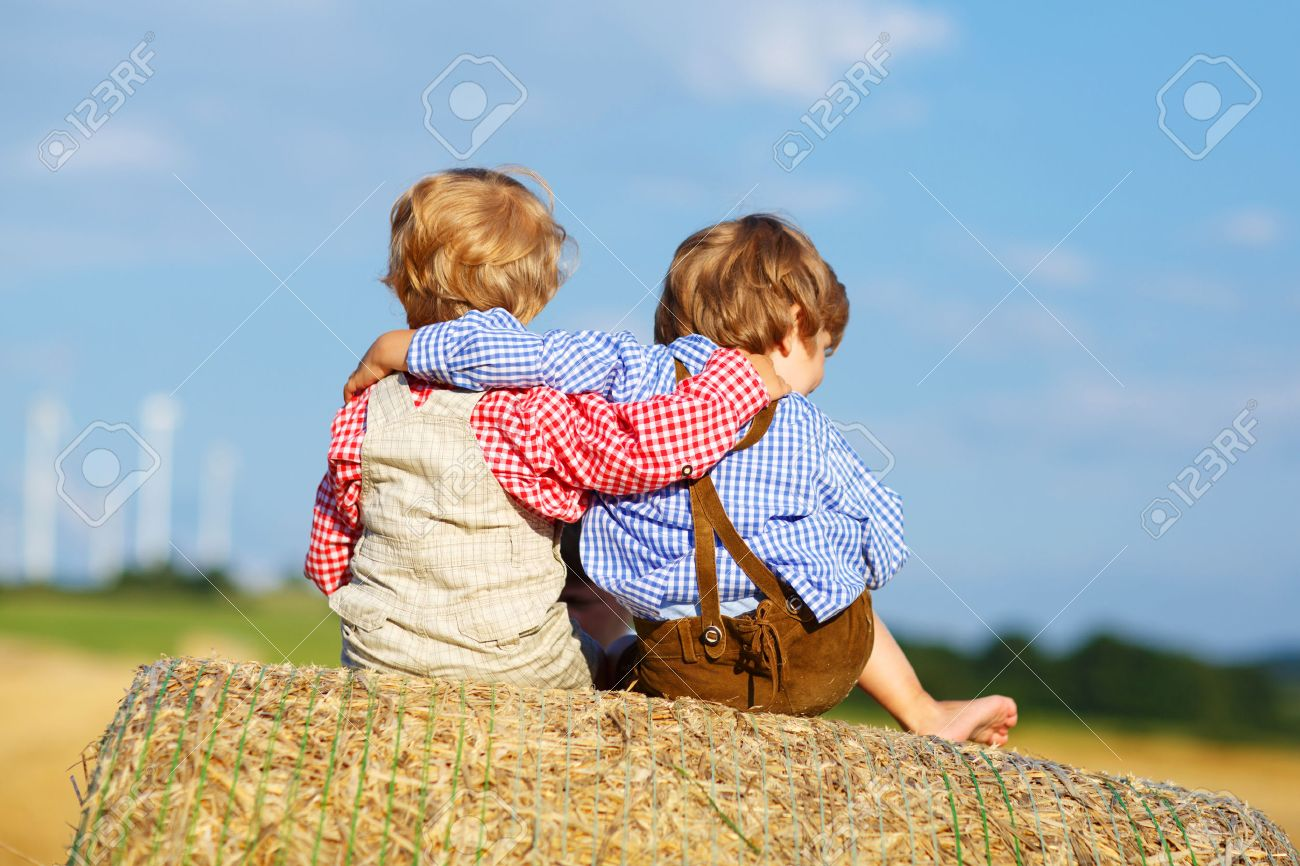 31563483-two-little-children-and-friends-sitting-on-hay-stack-or-bale-and-speaking-on-yellow-wheat-field-in-s